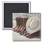 Cowboy hat on row of cowboy boots outside a log fridge magnets