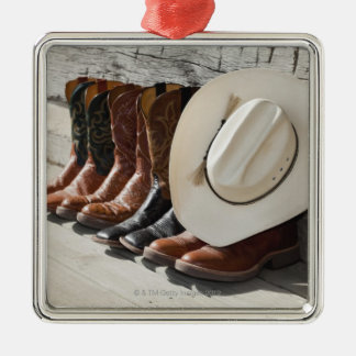 Cowboy hat on row of cowboy boots outside a log metal ornament
