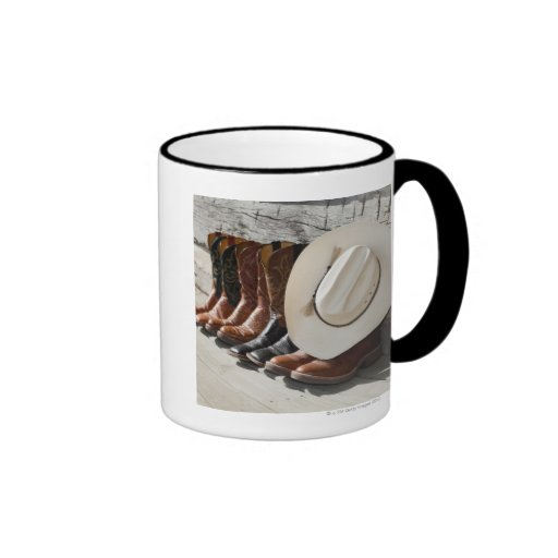 Cowboy hat on row of cowboy boots outside a log ringer coffee mug