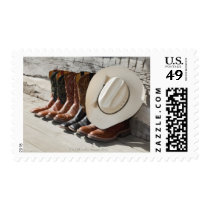 Cowboy hat on row of cowboy boots outside a log postage