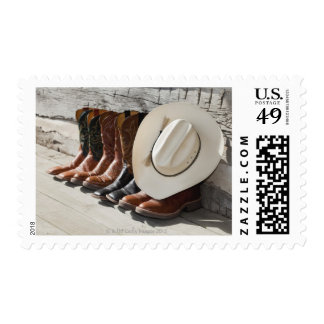 Cowboy hat on row of cowboy boots outside a log stamps