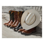 Cowboy hat on row of cowboy boots outside a log posters