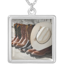Cowboy hat on row of cowboy boots outside a log silver plated necklace