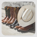 Cowboy hat on row of cowboy boots outside a log square sticker