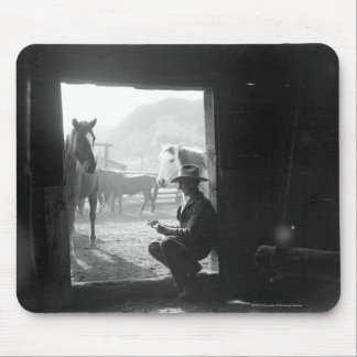 Cowboy in a doorway with horses mouse pad