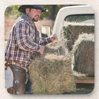 Cowboy lifting bales of hay coaster