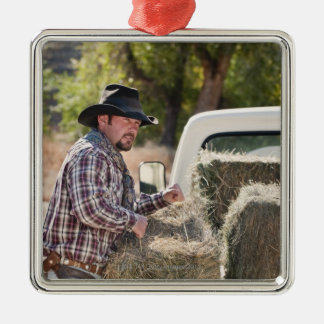 Cowboy lifting bales of hay metal ornament
