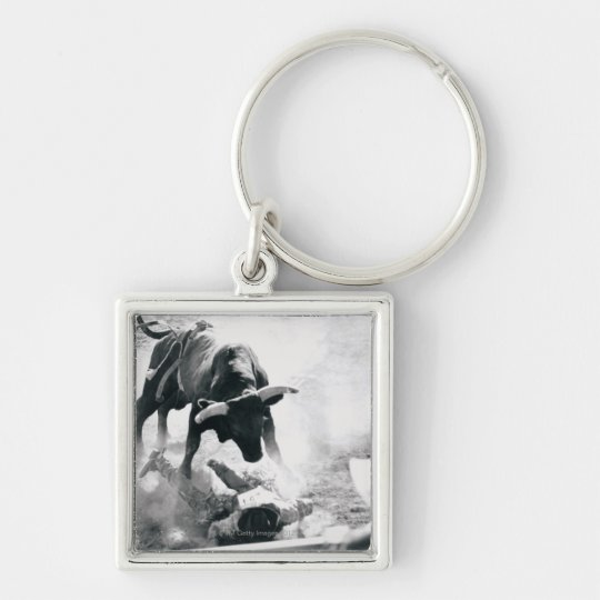 Cowboy on ground after falling off bull keychain