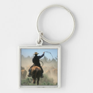 Cowboy on horse with lasso driving cattle keychain