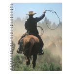Cowboy on horse with lasso driving cattle note books