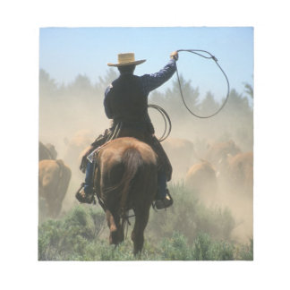 Cowboy on horse with lasso driving cattle notepad