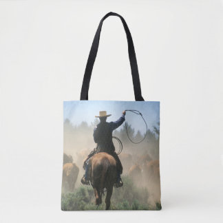 Cowboy on horse with lasso driving cattle tote bag