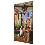 Cowboy posing with lasso and pet dog canvas print