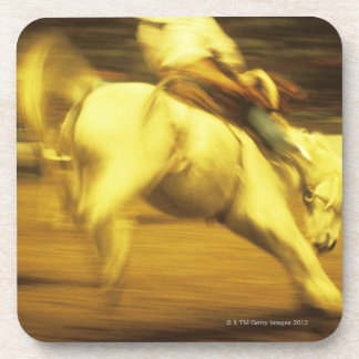 Cowboy riding bucking bronco in rodeo, side view drink coasters