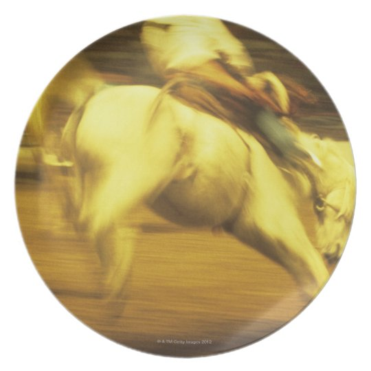 Cowboy riding bucking bronco in rodeo, side view melamine plate