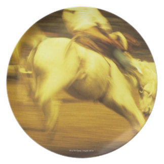 Cowboy riding bucking bronco in rodeo, side view dinner plate