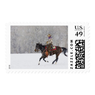 Cowboy riding in snowfall postage