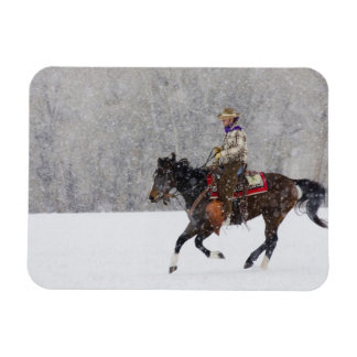 Cowboy riding in snowfall rectangle magnet