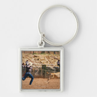 Cowboy roping calf in rodeo keychain