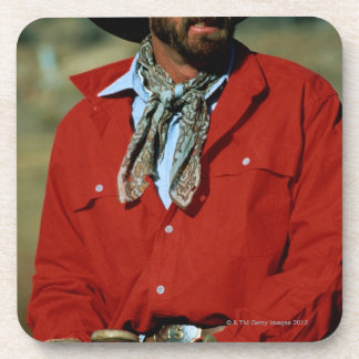 Cowboy sitting on horse wearing red shirt, drink coaster