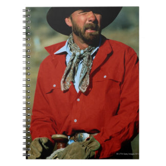 Cowboy sitting on horse wearing red shirt, notebook