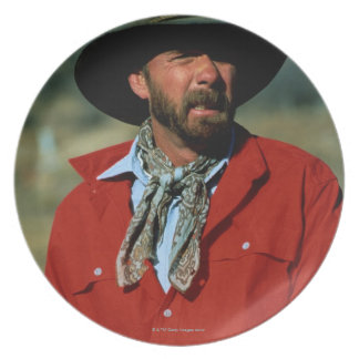 Cowboy sitting on horse wearing red shirt, plate