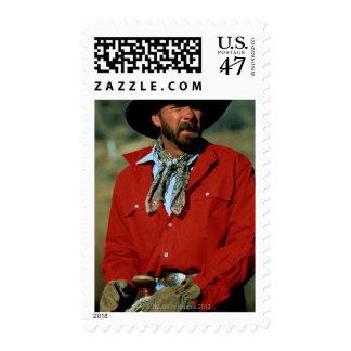 Cowboy sitting on horse wearing red shirt, postage