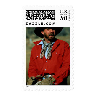 Cowboy sitting on horse wearing red shirt, postage