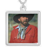 Cowboy sitting on horse wearing red shirt, square pendant necklace