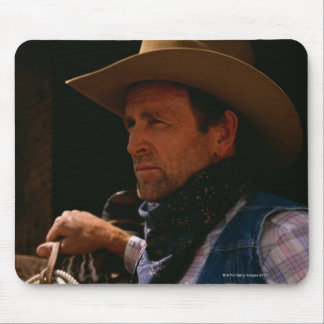 Cowboy standing by saddle with rope mouse pad