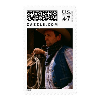 Cowboy standing by saddle with rope postage stamp