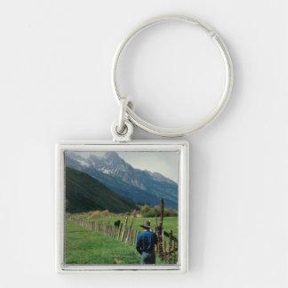 Cowboy walking along fenced pasture Teton Range Silver-Colored Square Keychain