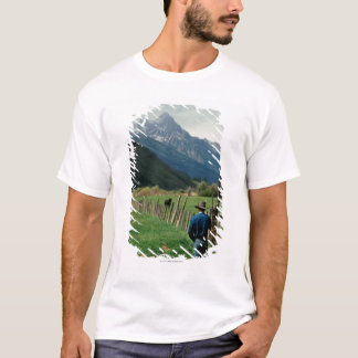 Cowboy walking along fenced pasture Teton Range T-Shirt