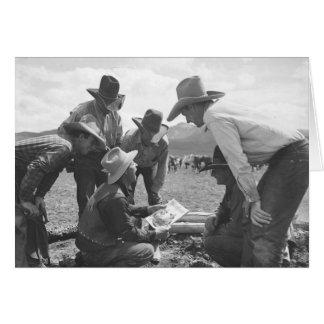 Cowboys looking at a magazine card