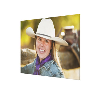 Cowgirl beside fence canvas print