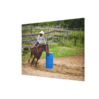 Cowgirl on horseback practicing barrel racing in canvas print