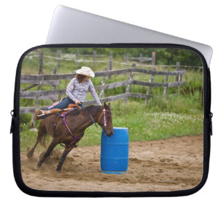 Cowgirl on horseback practicing barrel racing in laptop computer sleeves