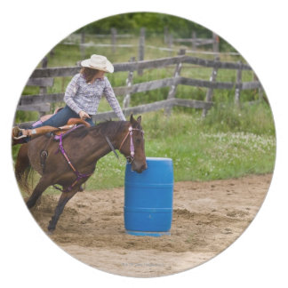 Cowgirl on horseback practicing barrel racing in party plate