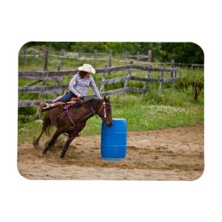 Cowgirl on horseback practicing barrel racing in rectangular photo magnet