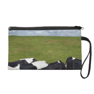 Cows in a pasture wristlet purses