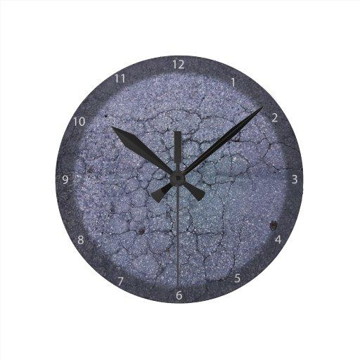 Cracks in asphalt pavement of walkway round clocks