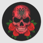 Cráneo albanés de la bandera con los rosas rojos etiqueta redonda