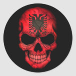 Cráneo albanés de la bandera en negro etiqueta redonda