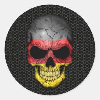 Cráneo alemán de la bandera en el gráfico de acero etiqueta redonda