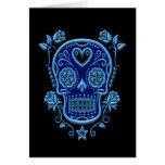 Cráneo azul del azúcar con los rosas en negro tarjetón