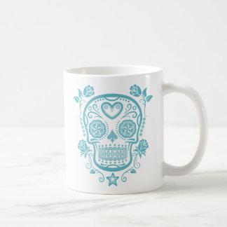 Cráneo azul del azúcar con los rosas taza de café