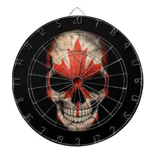 Cráneo canadiense de la bandera en negro tablero dardos