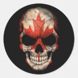 Cráneo canadiense de la bandera en negro pegatina redonda