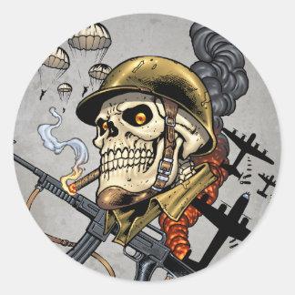 Cráneo con el casco, los aeroplanos y las bombas pegatina redonda