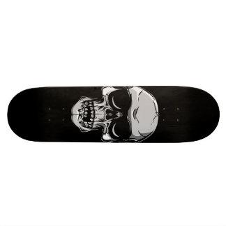 Cráneo con las gafas de sol en el monopatín negro skateboards
